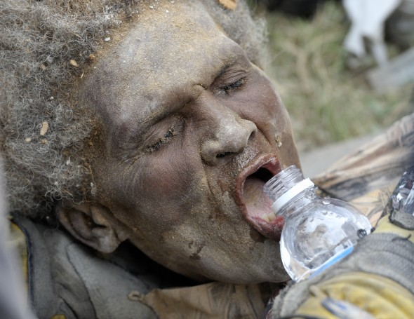Ena Zizi gets a drink of water after being pulled alive on January 19 from the rubble of Haiti's devastating earthquake