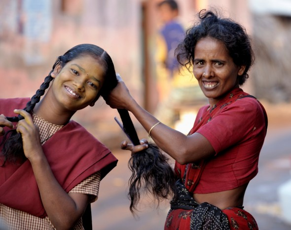 A mother braids her daughter's hair before she departs for school in Nallur, a small village in the state of Tamil Nadu