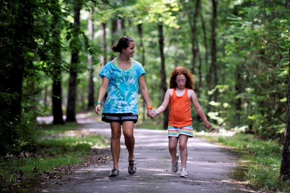 Counselor Madison Nix walks with camper Jalei Mannis along a path through the quiet woods at Camp Aldersgate