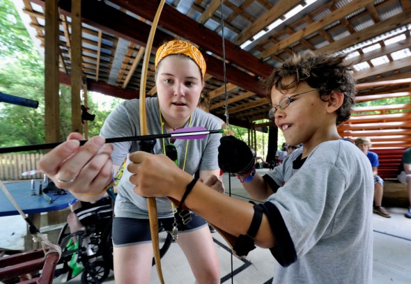 Counselor Morgan Butler helps camper Gavin Carney on the archery range at Camp Aldersgate