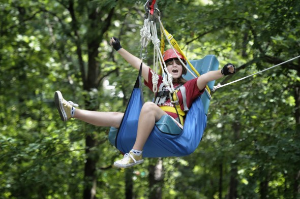 Camper Audrey Crosson celebrates as she rides a zip line through the forest canopy at Camp Aldersgate in Little Rock, Arkansas.