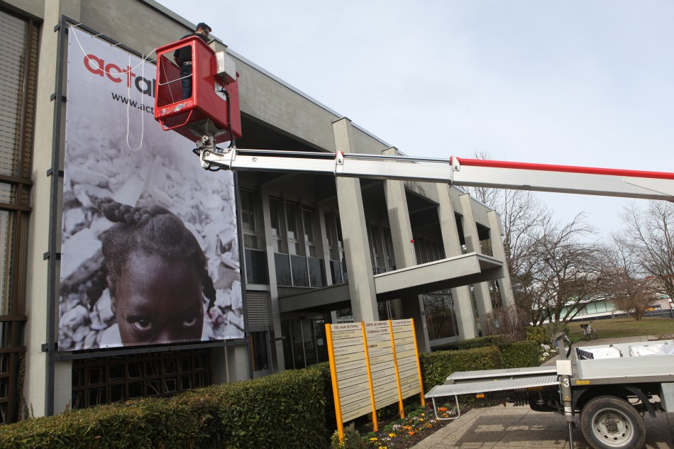 Hanging Paul Jeffrey's photo on WCC headquarters in Geneva - Photo by Sean Hawkey