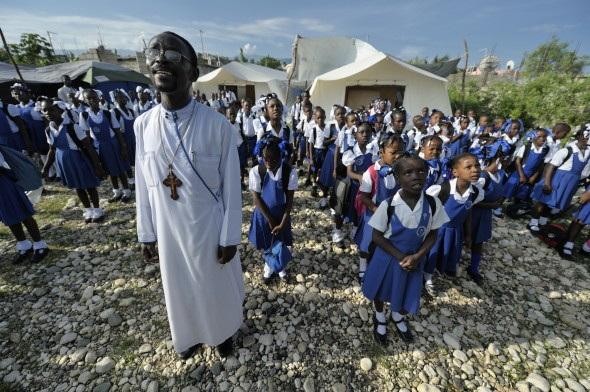 Father Jean-Chenier Dumais, a Russian Orthodox priest in Port-au-Prince, Haiti, stands with children of the Notre Dame de Petits school while they sing the national anthem as Haiti's flag is raised at the beginning of a school day. The school's building collapsed in the January 2010 earthquake, and classes are currently conducted in the large tents in the background.